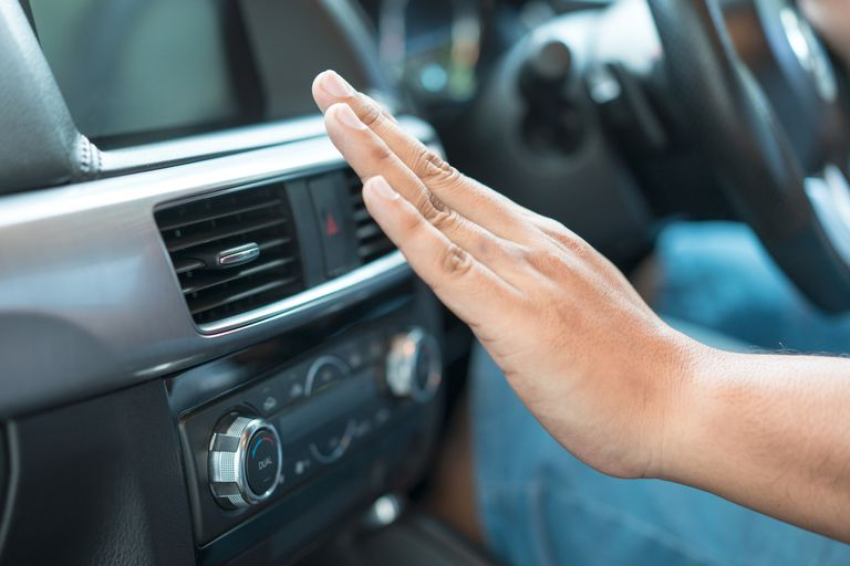 Photo of a hand in front of a car's ac/heater vents illustrating a corrective mobile A/C heater repair.