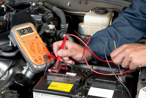 Mechanic using test meter to evaluate a car's battery.