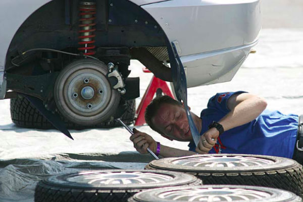 Photo of mobile mechanic working on rear axle/hub of a car.